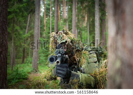 Masked soldier/sniper is aiming at the target during the mission (visible eye throught a telescope,color toned image) - stock photo