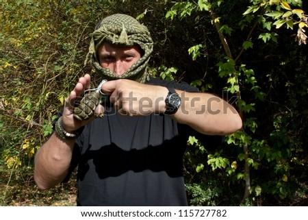 masked terrorist threatens to bomb exploding - stock photo