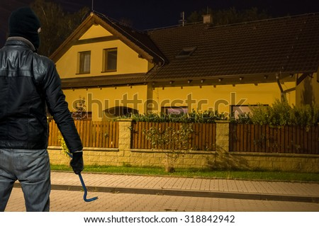 Masked thief in balaclava is going to steal and rob the house at night. - stock photo