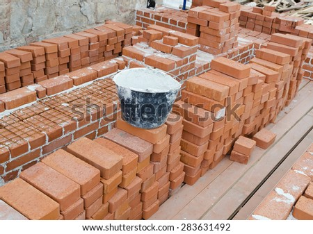 Mason bricklaying background with bucket of cement and clay brick blocks - stock photo