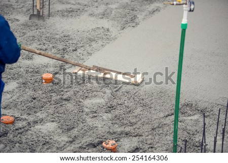 Mason building and leveling a first layer of fresh concrete floor at house foundation, construction site - stock photo