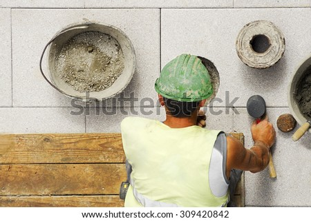 mason construction worker to repair  tiles slabs in  the sidewalk  at road in  the street city  - stock photo