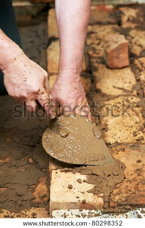 Mason hands at bricklaying works with trowel and clay brick blocks - stock photo