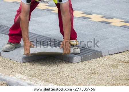 Mason hands laying paver bricks, paver making sidewalk. Selective focus and shallow dof. - stock photo
