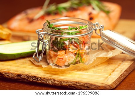 Mason jar with pieces of salmon with fresh cucumber and ruccola and served with parchment paper on wooden board in restaurant. Close up - stock photo