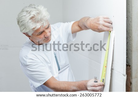 Mason measuring a wall - stock photo