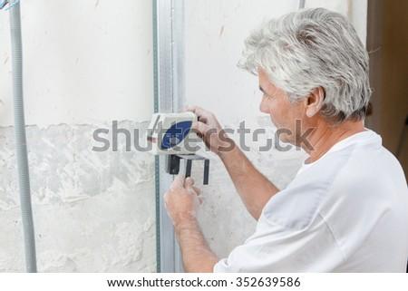 Mason measuring up a wall - stock photo