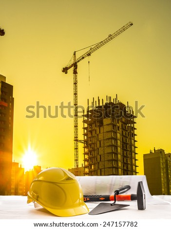 Mason tools yellow helmet hammer trowel lie blue print architect paper plan on table with sunset sky with building construction crane lift load against evening sun rise shine and new modern house - stock photo