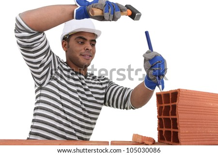Mason using chisel on brick - stock photo