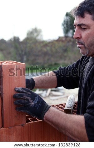 Mason working on unfinished brick wall - stock photo