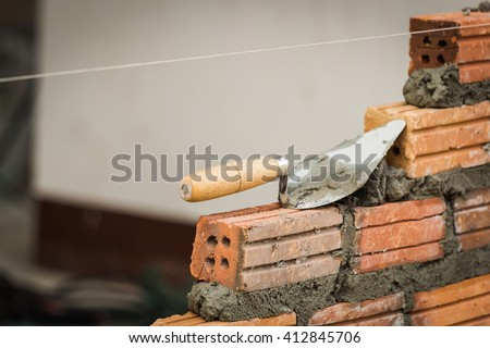 Masonry trowel is placed on a brick wall while waiting for the next class standards. A string orientation brick on top. - stock photo