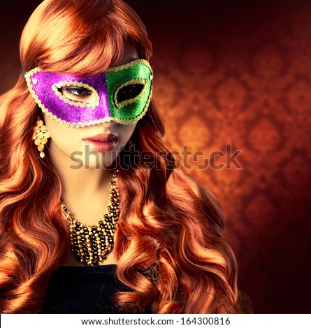 Masquerade. Beautiful Girl in a Carnival mask. Beauty Glamorous Woman Celebrating. Holiday Make up and Hairstyle. Long Red Wavy Hair - stock photo