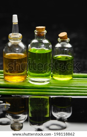 massage oil and set of green plant stem still life with reflection