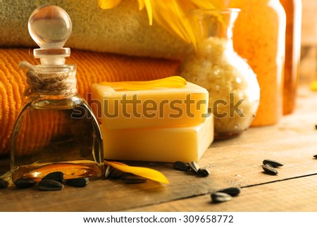 Massage oil and spa treatments, sunflower on wooden background - stock photo