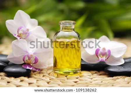 Massage oil and stones with white orchid with stones on mat