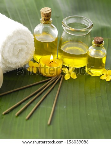 Massage oil and yellow flower and candle,towel on green banana leaf