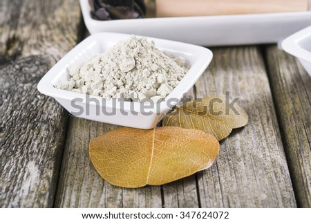 massage spa setting: cosmetic clay on old wood table background