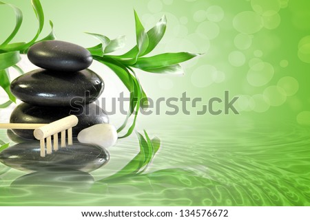 Massage stones black with bamboo plant behind and wooden rake