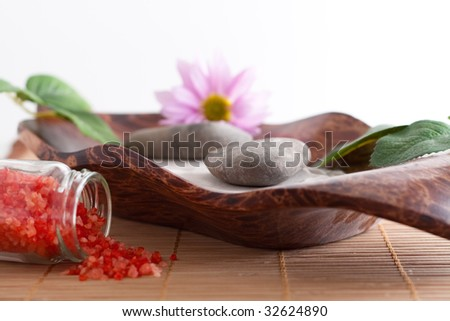 Massage stones on sand in a bowl, a purple flower and red bath salt isolated on white background - stock photo