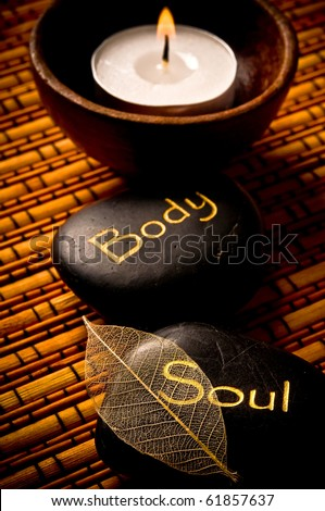 massage stones - relax, body, soul - and a candle over bamboo background like a concept for wellness, reiki and yoga symbols - stock photo