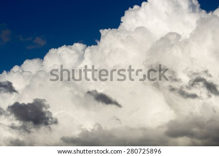 Masses of  majestic white fluffy cumulus  congestus or towering cumulus ice cream  clouds  with lower dark nimbus clouds in a blue Australian sky in late autumn  herald a shower of rain coming.