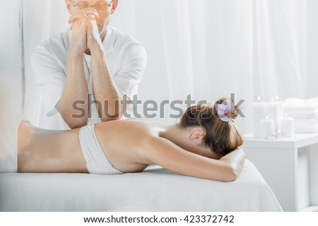Masseur and woman lying in light interior during therapeutic massage - stock photo