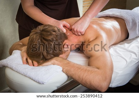 Masseur doing back massage on man body in the spa salon  - stock photo