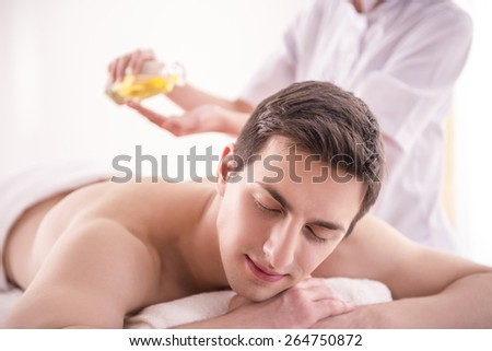 Masseur doing massage on man body with spa oil in beauty salon. - stock photo