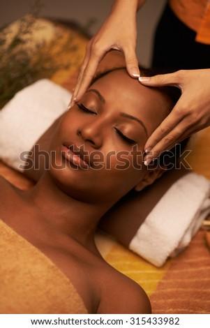 Masseur giving woman amazing scalp massage - stock photo