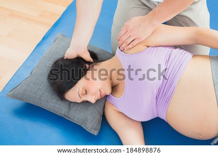 Masseur moving pregnant womans neck and shoulder in a fitness studio - stock photo