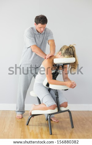 Masseur treating clients back in massage chair in bright room - stock photo