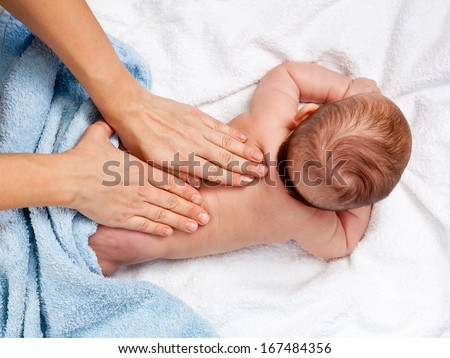Masseuse massaging 5 months infant - stock photo