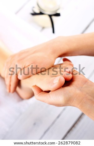 Masseuse massaging woman's foot..Woman in a beauty salon for pedicure and foot massage. - stock photo