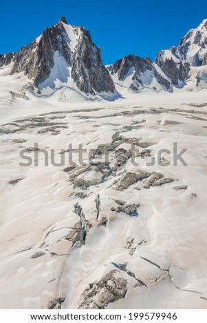 Massif de mont Blanc on the border of France and Italy. In the foreground the ice field and crevasses of the Valley Blanche - stock photo
