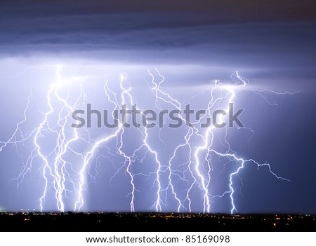 Massive colorful cloud to ground crazy skies lightning bolts hitting the horizon of city lights. - stock photo