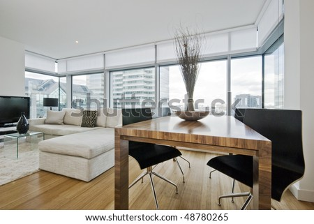 massive luxury living room with floor to ceiling windows and city views - stock photo