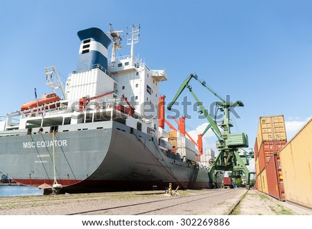 Massive port cranes are loading container ship with cargo at container terminal at Varna port, Varna, Bulgaria, May 16, 2014.