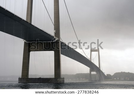 Massive rainfall on suspension bridge and Little Belt in Denmark. - stock photo