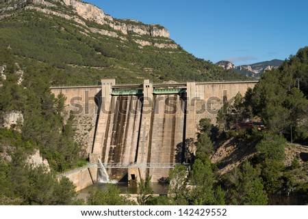 Massive reservoir dam amidst pine tree forested hills