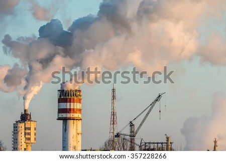 Massive white smokes coming out of many factory chimneys. Achema factory is a leading producer of nitrogen fertilizers and chemical products in Lithuania and the Baltics - stock photo