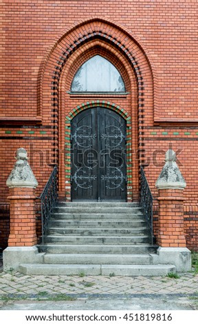 Massive wooden church door with a handle forged with an iron grip settled into a brick wall at the church. Breclav. South Moravia - stock photo