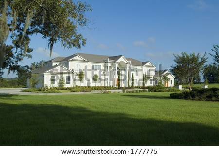 Massively large custom home or mansion with grand lawn and landscaping. - stock photo