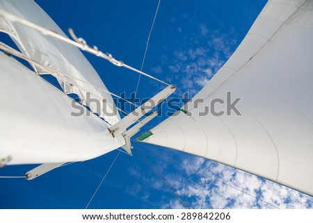 Mast and sail against the sky with clouds. - stock photo