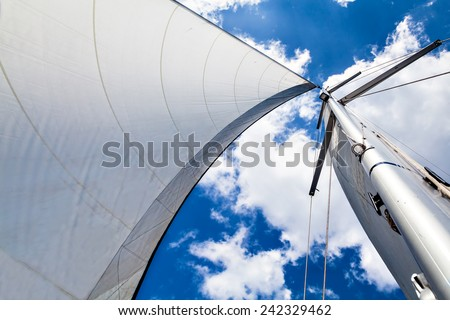 Mast and sail against the sky with clouds. Mast and sail against the sky with clouds on a sunny day. Bottom view. - stock photo