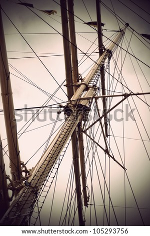 mast of old sailing ship in sepia - stock photo