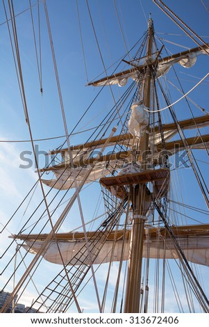 Mast of sail ship in blue sky - stock photo