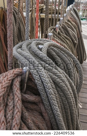 Mast, sail ropes and belaying pins on the deck of the a Tall Ship sailing vessel. - stock photo
