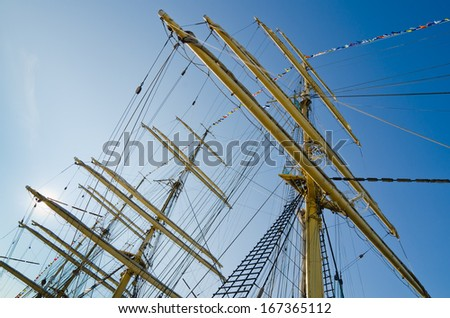 Mast with sails of an old sailing vessel - stock photo
