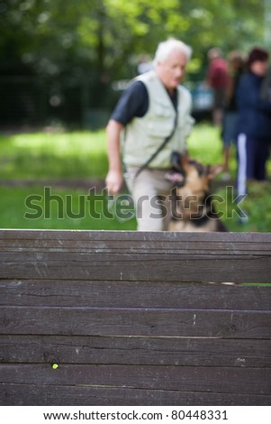 Master and his obedient (German shepherd) dog at a dog training center - stock photo