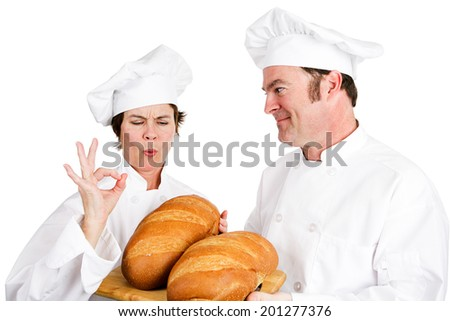 Master baker compliments a chef trainee on his perfect loaves of bread.  Isolated on white.